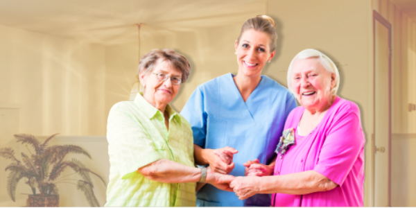 caregiver and two senior women smiling
